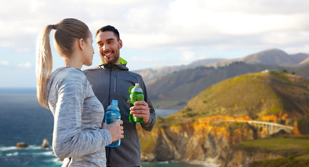 fitness, sport and people concept - smiling couple with bottles of water over bixby creek bridge on big sur coast of california background