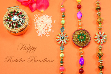 Celebrating Indian hindu festival Raksha Bandhan. Colorful Rakhi with flowers and rice on a orange background.