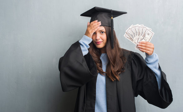 Young brunette woman over grunge grey wall wearing graduate uniform holding dollars stressed with hand on head, shocked with shame and surprise face, angry and frustrated. Fear and upset for mistake.