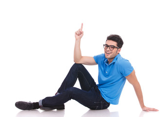 casual young man lying on the floor is pointing up