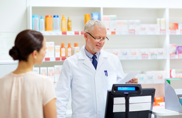 medicine, healthcare and people concept - senior apothecary reading prescription from customer at pharmacy