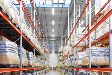 logistic, storage, shipment and industry concept - cargo storing at warehouse shelves