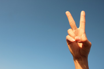 woman raising two fingers up on hand it is shows peace strength fight or victory symbol and letter V in sign language on sky.