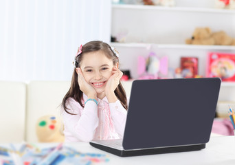 little girl sitting in front of open laptop in her room