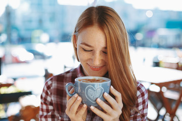Girl holding with arms a big cup of coffee