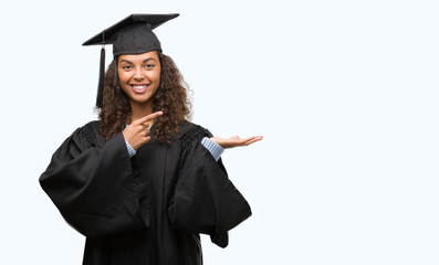 Young hispanic woman wearing graduation uniform very happy pointing with hand and finger