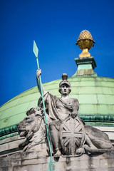 Britannia, personification of Britain, holding a Union Jack Shield, spear and the protection of a lion. London UK.
