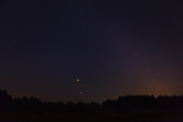 Night sky over forest, visible full eclispse of Moon, Mars in perigee and Milky Way
