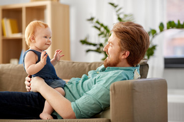 family, fatherhood and people concept - happy red haired father with little baby daughter at home