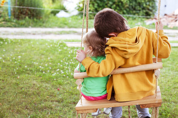 children sitting on a swing in the garden. older brother hugging little sister