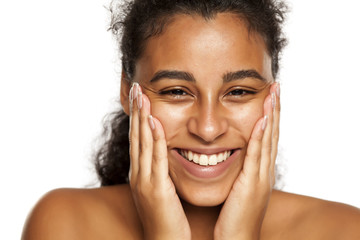 portrait of a happy young dark-skinned woman applying cream on her face on a white background