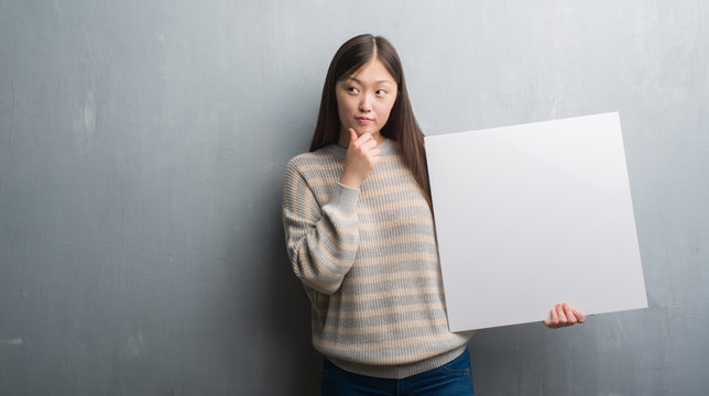 Young Chinese woman over grey wall holding banner serious face thinking about question, very confused idea