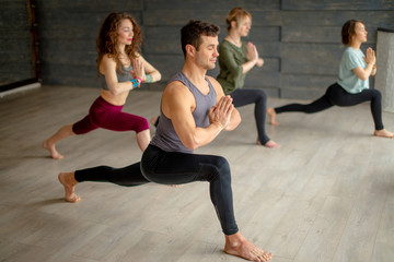 Group of caucasian women practicing yoga lesson with male instructor, standing in Warrior posture exercise, indoor fitness studio with grey background