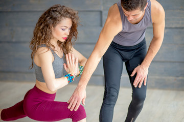 Young beautiful lady with long curly hair doing yoga practice with private trainer at fitness hall over grey background. Yoga master helps pupil to perform Warrior pose