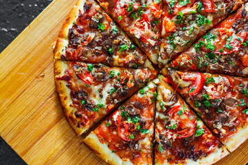 sliced Pizza with Mozzarella cheese, mushrooms, Tomatoes, pepper, Spices and Fresh Basil. Italian pizza.