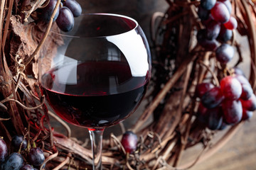 Glass of red wine with grapes and dried  leaves.