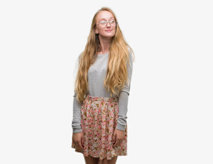 Blonde teenager woman wearing flowers skirt smiling looking side and staring away thinking.