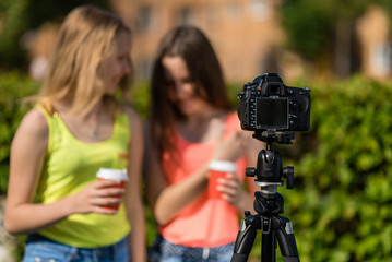 Two girlfriends girl bloggers. Summer in nature. Writes the video to the camera. Free space for text. Blurred background.