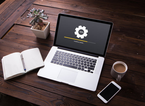View of Installing update process with gearbox percentage progress and loading bar on laptop / computer with smartphoneand office equipment on wooden desk background
