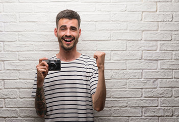Young man holding vintage camera standing over white brick wall screaming proud and celebrating victory and success very excited, cheering emotion