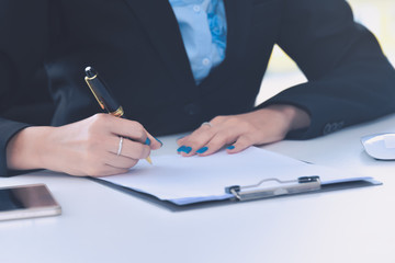Close up business woman hand signing contract document