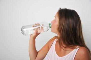 brünette frau trinkt bei hitze im sommer wasser aus flasche