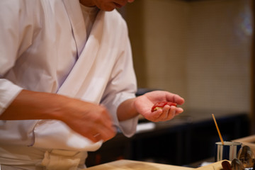 Professional sushi chef carefully using just the right pressure to make perfect sushi with confident and dedication. Precision and Finesse at its best practice to achieve top performance in business.