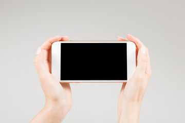 Female holding white smartphone with blank screen in two hands hand