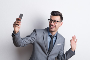 Portrait of a young man with smartphone in a studio, taking selfie.
