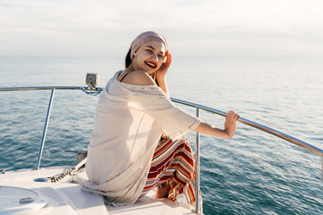 happy young girl in trendy summer pants enjoys a holiday on her yacht in the rays of the evening sun