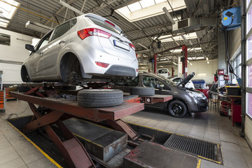Car on a lift in a repair shop with tires. Professional service
