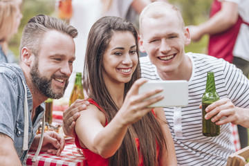 Happy friends drinking beer and taking selfie during grill party