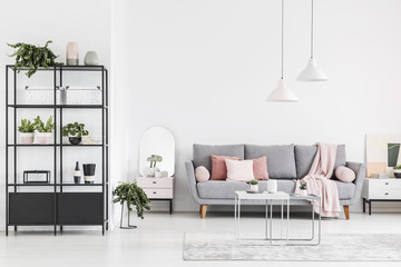 Lamps above table in white spacious living room interior with grey sofa with pink blanket. Real photo