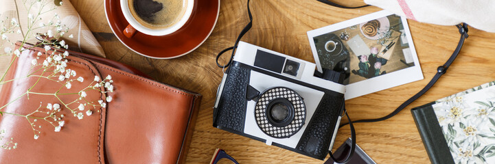 Top view of a vintage, film camera and a polaroid picture on a wooden table with a cup of coffee and a leather bag