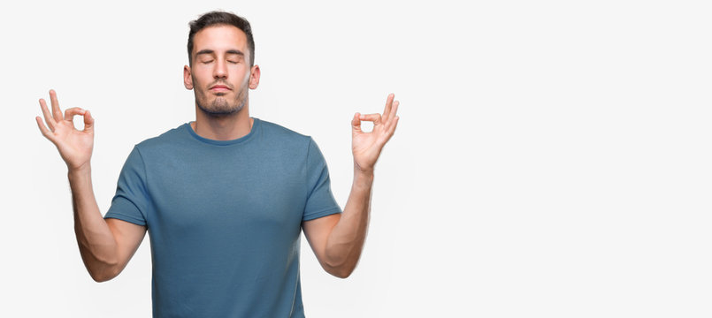 Handsome young casual man relax and smiling with eyes closed doing meditation gesture with fingers. Yoga concept.