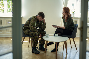 Depressed soldier and his psychotherapist during a session. View through a door