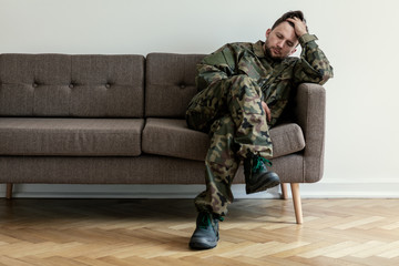 Helpless soldier sitting on a couch while waiting for a therapy session