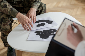 Close-up of soldier's hands touching papers with ink stains during a therapy