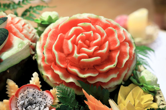 Closeup of Fruits carve shape beautiful flowers, from Watermelon, Dragon Fruits, with lotus and tree leafs. Thai traditional art concept.