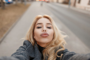 Fashionable young beautiful girl with big lips sends an air kiss and makes a photo of selfie on the street