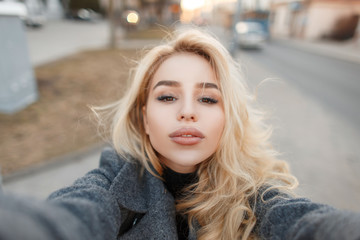 Sexy young woman with her lips doing selfie in the city