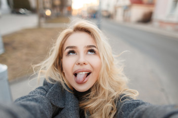 Funny young happy woman in a gray fashion coat makes selfie outdoors