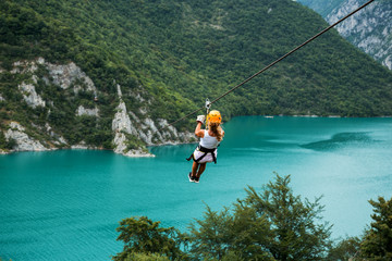 Woman sliding on a zip line over the blue lake