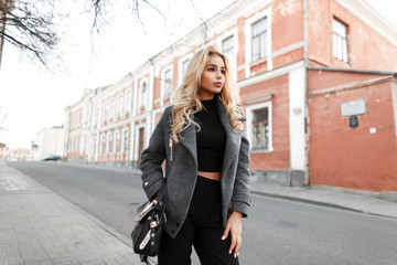 Pretty young woman model with a stylish black handbag in a fashion jacket walking on the street Fotomurales
