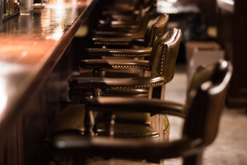 Bar design in classic vintage style. Oak wooden bar counter, comfortable chairs with leather upholstery and cooper rivets. Luxury interior. Great place for relax after work.