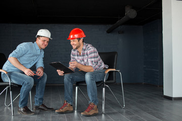 positive engineers with blueprint are sitting on the chairs at work. full length photo. copy space
