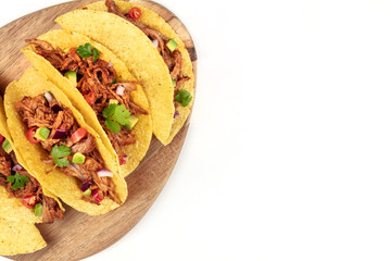 Overhead closeup photo of Mexican tacos with pulled pork, avocado, chili peppers, cilantro, with place for text, on white