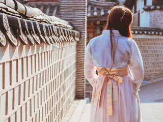travel and tourist asia concept from backside long hair woman in korea traditional cloth (hanbok) relax, take picture in vintage town with rim light and soft focus background