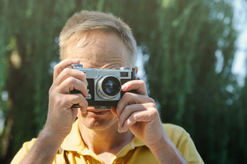 The man is photographing an old camera.