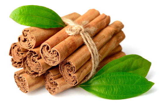 bunch of cinnamon sticks with fresh leaves isolated on the white background